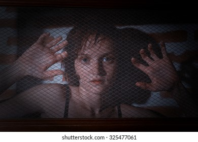 Terrified girl behind a dense metal grid grabbing it with her hands