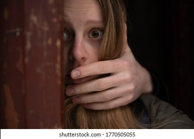 Terrified girl with big brown eyes outside the door, hand covering her face, fighting violence, social program to rescue women, cry