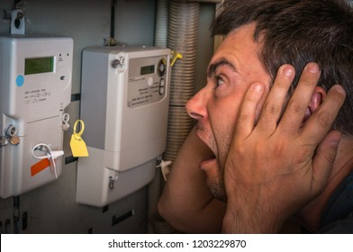 Terrified man is checking electricity meter - consumption and expensive electricity concept