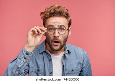 Terrified man dressed casually, stares through glasses, being surprised find out about his success. Male doesn`t believe his own luck, isolated over pink background. Emotions, people concept