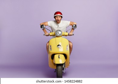 Terrified moped driver drives on high speed in helmet, stares at camera, wants to be in time, delivers something for customers, works as courier, isolated on purple background. Transportation concept