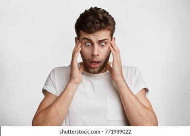 Terrified shocked male looks with bugged eyes down, sees something awful, can`t believe his eyes, being in stupor, keeps hands on temples, isolated over white studio background. Emotions concept