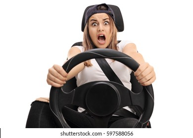 Terrified teenage girl holding a steering wheel and pressing the brake pedal isolated on white background