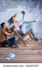 Terrified woman on toppling chair, man trying to catch her