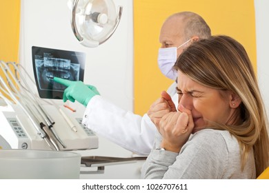 Terrified young female patient at the dentist office looking to dental x ray with doctor