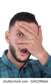 A terrified young man covering his face with his palm shown only one open eye, trying to not see, opening his mouth, isolated on a white background.