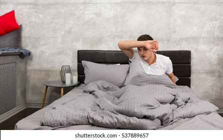 Terrified young man woke up from a nightmare and wiping sweat from his forehead while sitting in stylish bed with grey colors in a bedroom in loft style