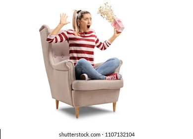 Terrified young woman with a box of popcorn sitting in an armchair isolated on white background
