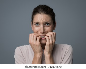 Terrified young woman looking at camera, she is feeling scared and shaking