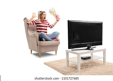 Terrified young woman with a popcorn box seated in an armchair watching television isolated on white background