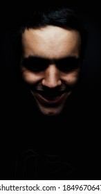 terrifying face with very marked features of young boy with terrifying smile with black background. scary face of teenager with black and brunette hair