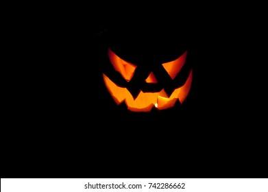a terrifying halloween pumpkin illuminates the darkness around it