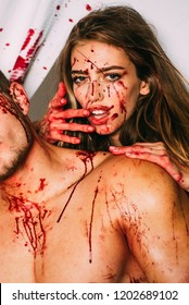 Terrifying zombie couple. Blood is flowing down the neck, bite marks are visible. A terrible Halloween episode, the girl bites her boyfriend by the neck, with blood on her face and blood lust