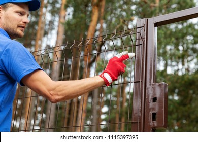 territory enclosure - worker installing metal fence