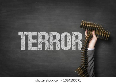 Terror text on blackboard with businessman hand holding ammunition