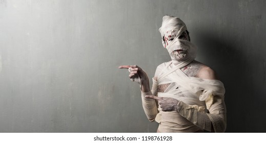 Terrorific mummy pointing to the lateral on textured wall background.  Halloween holidays
