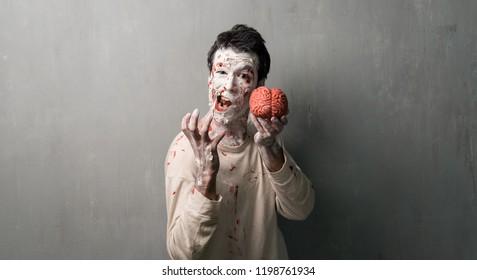 Terrorific zombie eating a brain.  Halloween holidays