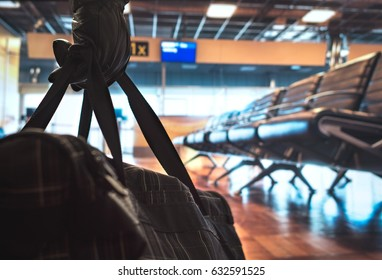 Terrorism in aiport. Dangerous terrorist planning a bomb attack in the waiting area and gate. Holding suspicious black bag with leather gloves. Anonymous criminal. Safety and security threat concept.