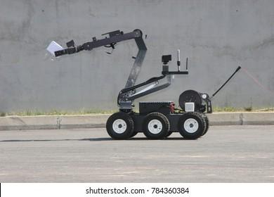 Terrorism. Bomb. Robot. A robot disarm a bomb inside a car of terrorists. Bomb squad robot