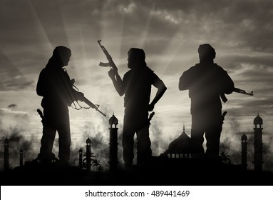 Terrorism and conflict. Armed terrorists on the background of a mosque in the smoke