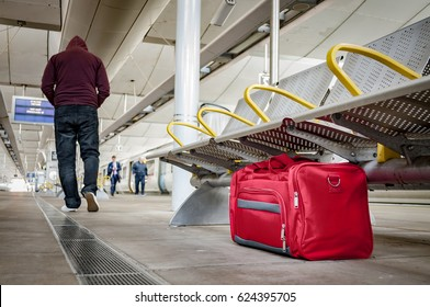 Terrorism and public safety concept with an unattended bag left under chair on platform at train station or airport and man wearing a hoodie walking away from the suspicious item (possibly terrorist)