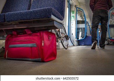 Terrorism and public safety concept with an unattended bag under a chair on a train wagon, monorail or subway cart and man wearing a hoodie walking away from the suspicious item (possibly terrorist)
