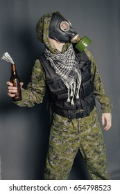 The terrorist in a camouflage suit, body armor and gas mask throws hammers a cocktail with an incendiary mixture. Studio photo on a gray background.