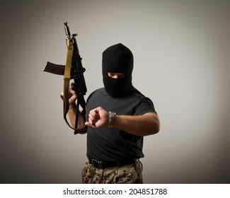 Terrorist with gun looking at his wristwatch. Time concept.