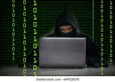 Terrorist hacker in black jacket try to hack data from internet by using computer notebook with binary code digit in background.