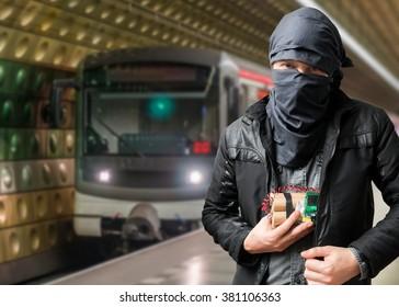 Terrorist has dynamite bomb in jacket. Train approaching underground station. Terrorism concept.