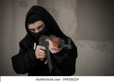 Terrorist hold a rifle aiming eye contact with blurred background.