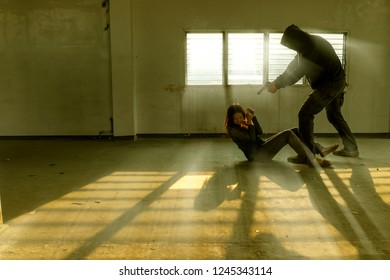 terrorist man or criminal holding hand gun threatening with taking Asian woman as hostage or kidnapping in abandoned building. Rape, terrorism, crime, violence, robbery and killer concept. film tone