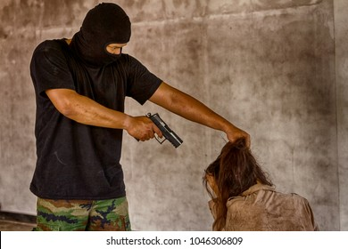 A terrorist man in mask holding gun kidnapping young women for a hostage in abandoned building.