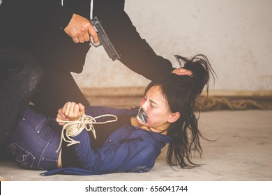 A terrorist man in mask holding gun kidnapping young women for a hostage in abandoned building. Rape, terrorism, crime, violence, robbery and killer of women conception.