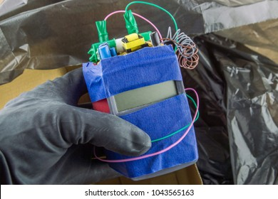 the terrorist threat: the hand of a terrorist preparing a homemade bomb to use