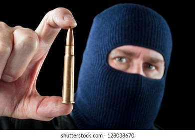 A terrorist wearing a ski mask as a disguise holds out a large automatic rifle bullet.