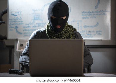 Terrorist working on his computer. Concept about international crisis, war and terrorism