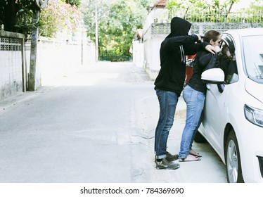 terrorist,Masked robber or Criminals or dangerous man or thief holds gun or pistol threaten teenage victim and kidnap or tries to steal a car on outdoor parking