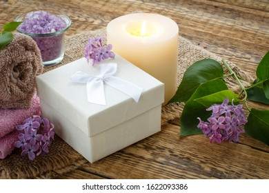 Terry towel for bathroom procedures, white gift box, sea salt, burning candle and lilac flowers on sackcloth and old wooden boards. Spa products and accessories.