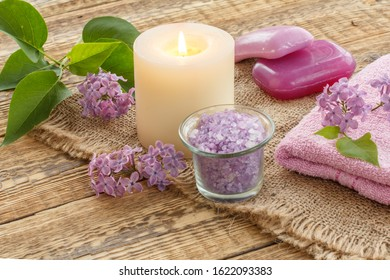 Terry towel, soap for bathroom procedures, sea salt, burning candle and lilac flowers on sackcloth and old wooden boards. Spa products and accessories.