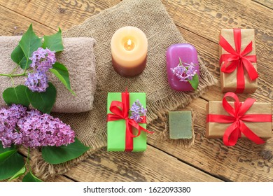 Terry towels, soap for bathroom procedures, burning candle, gift boxes and lilac flowers on sackcloth and old wooden boards. Top view. Spa products and accessories.