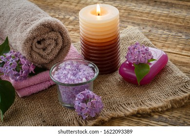 Terry towels, soap for bathroom procedures, burning candle and lilac flowers on sackcloth and old wooden boards. Spa products and accessories.