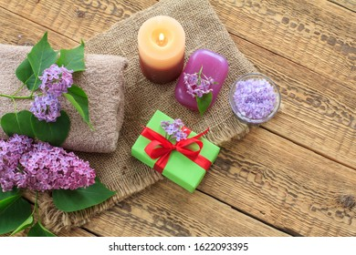Terry towels, soap and sea salt for bathroom procedures, burning candle, gift box and lilac flowers on sackcloth and old wooden boards. Top view. Spa products and accessories.