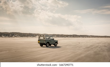 Terschelling, Holland - 8 march 2020: Land Rover Defender on North Sea beach. The iconic and legendary Land Rover Defender was issued in 1983.
