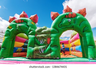 Teruel, Spain - April 22, 2019: Bouncy castle in the shape of dinosaurs in a children's playground outdoors.
