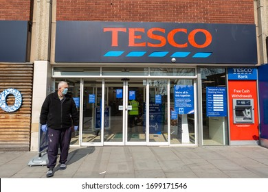Tesco entrance during Covid-19 pandemic restrictions. Customer with surgical mask and disposable gloves walking out.Social distancing rules and limits for shopping Tesco Bank ATM. London UK 09/04/2020