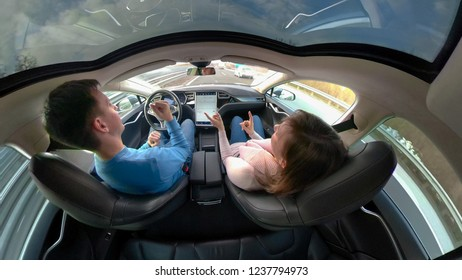 TESLA AUTONOMOUS CAR, March 2018 - CLOSE UP: Carefree couple dancing while driving in an autonomous Tesla car. Reckless man and woman driving and not paying attention to road in self steering vehicle.