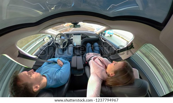 TESLA AUTONOMOUS CAR, March 2018 - CLOSE UP: Young couple sleeps while cruising down a highway in a high tech self driving car. Careless woman and man enjoying a relaxing road trip in autonomous Tesla