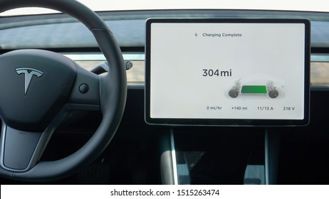 TESLA CAR, VIENNA, AUSTRIA, JULY 2019: CLOSEUP Touchscreen inside autonomous Tesla vehicle notifies car battery is fully charged. High tech tablet showing the futuristic electric car's battery is full