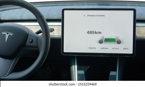 TESLA, VIENNA, AUSTRIA, JULY 2019: CLOSEUP Touchpad inside Tesla car displays the battery charging is complete. High tech autonomous car is fully charged. Futuristic car interior with tablet display